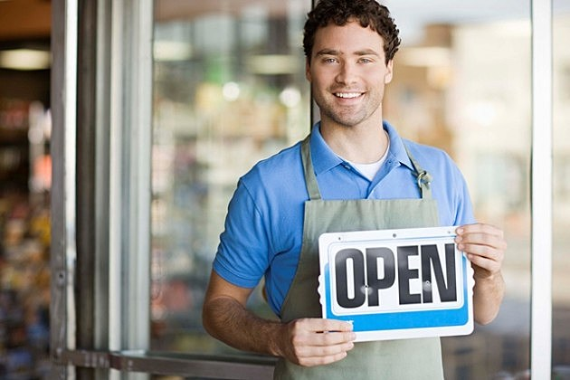 Shopkeeper smiling by storefront with open sign