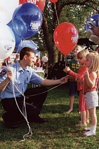 Police officer hands out balloons at National Night Out.