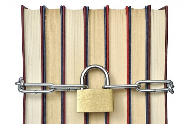 Books and padlock with chains isolated on white