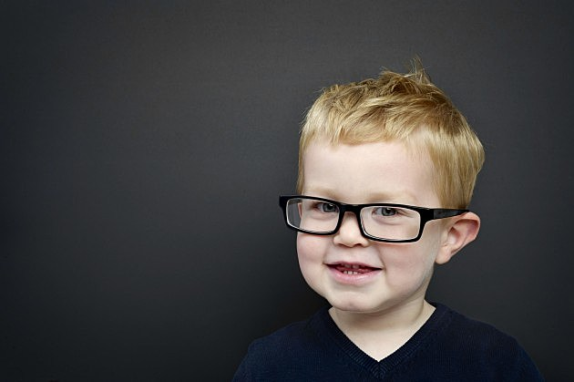 Smart young boy wearing glasses in front of a blackboard