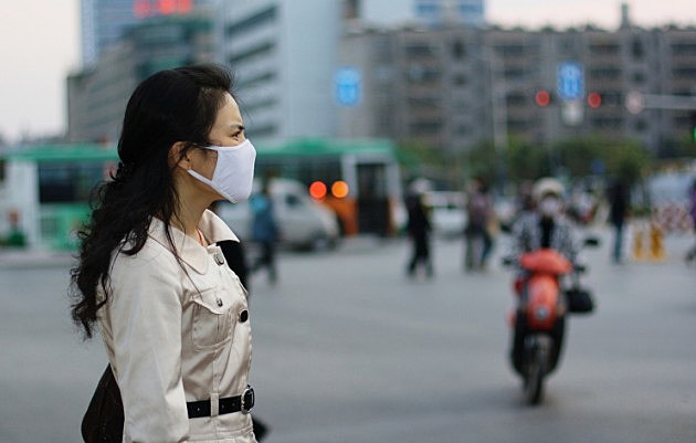Woman wearing a face mask against pollution or disease