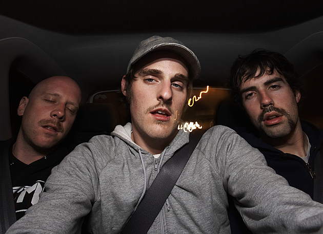 Three young men riding in car, night, portrait
